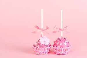Two cake pops with pink glaze