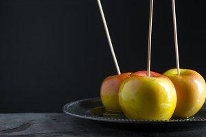 Three shiny caramel apples on a tin plate