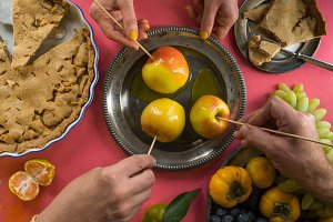 Caramel apples, American apple pie, hands over the table