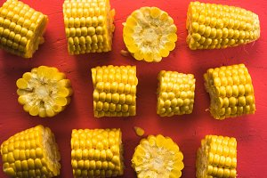 Pattern from different pieces of corn on a pink table