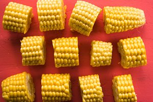 Different pieces of fresh corn on a pink table close-up