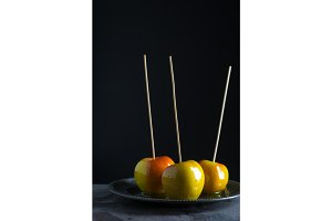 Three shiny caramel apples on a tin plate side view