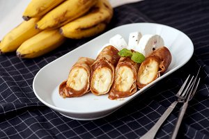 Caramel banana wrapped in a pancake with a sauce
