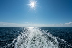 Sun shining over the wake of cruise ship at sea
