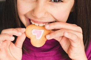 Little girl biting a heart cookie