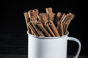 Porcelain cup full of cinnamon sticks