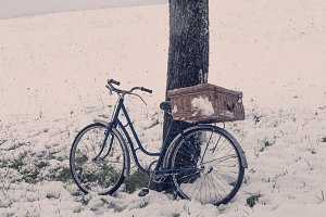 Vintage bicycle with suitcase. Snow