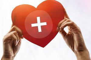 hands holding heart cross symbol