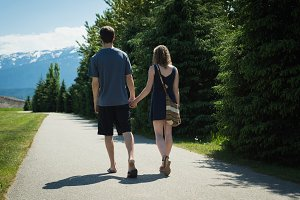 Couple holding hands and walking on countryside road on a sunny day