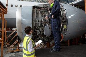 Male aircraft maintenance engineers examining turbine engine of aircraft