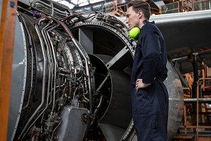 Male aircraft maintenance engineer examining turbine engine of aircraft