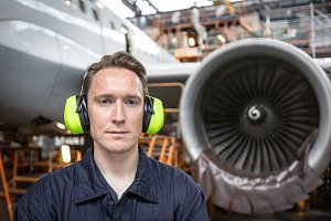 Male aircraft maintenance engineer standing at airlines maintenance facility
