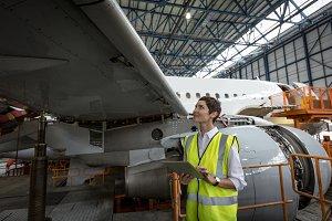 Female aircraft maintenance engineer examining engine of airplane