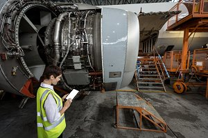 Female aircraft maintenance engineer examining turbine engine of airplane