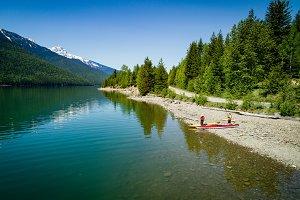 Couple with kayak on lakeshore