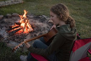 Woman playing guitar near campfire at campsite