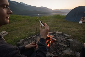 Man cooking sausage on campfire