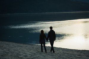 Couple walking with hand in hand near lake