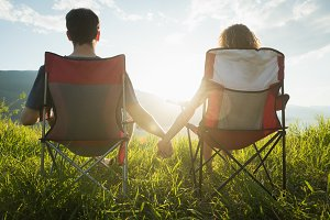 Couple sitting with hand in hand at campsite