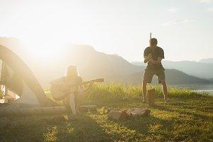 Woman playing guitar while man splitting log at campsite