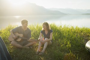 Man playing guitar for his wife at campsite