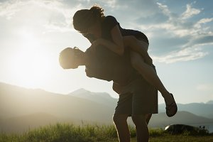 Man giving piggyback ride to his partner in countryside