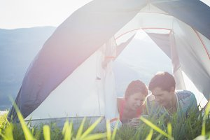 Couple using mobile phone in tent