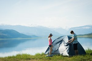 Couple putting up a tent in countryside