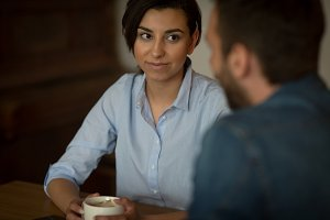 Woman looking at man while having coffee