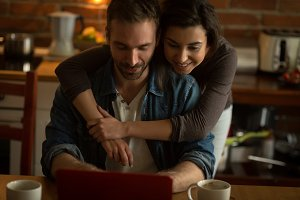 Woman embracing man using laptop