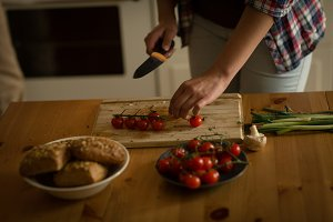 Mid section of woman cutting cherry tomatoes