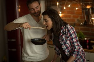 Man feeding food with wooden spoon to woman