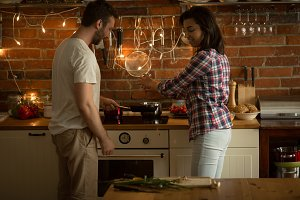 Happy couple preparing food at home