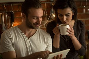 Man showing tablet computer to woman having coffee