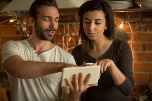 Couple using tablet in kitchen