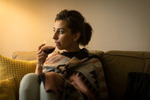 Thoughtful woman having drink while sitting on sofa