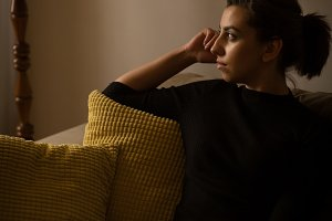 Thoughtful woman sitting on sofa