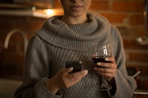 Mid section of woman using phone while holding wineglass