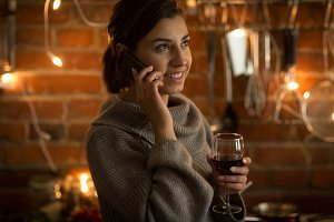 Woman talking on phone while holding wineglass