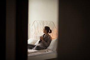 Woman having drink seen through doorway