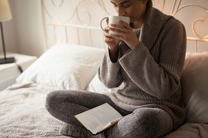 Full length of woman having coffee while sitting with book