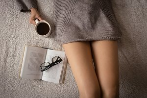 Mid section of woman holding coffee cup while lying on bed