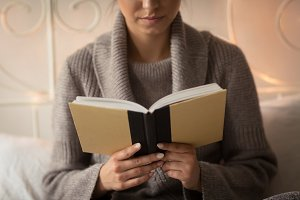 Mid section of woman reading book
