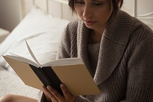 Close up of woman reading book at home