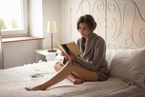 Woman reading book while sitting on bed