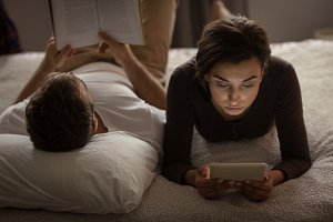 Man reading book while woman using tablet at home