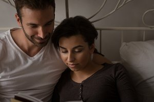 High angle view of young couple reading book in bed
