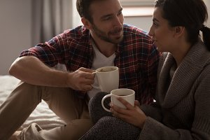 Happy couple having coffee in bedroom