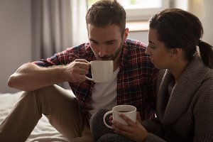 Couple having coffee in bedroom