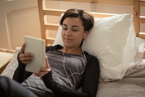 Young woman using tablet while lying on bed
